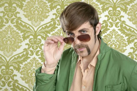 Image shows man with wearing 70s inspired clothing and facial hair standing in front of a retro wallpaper background