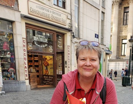 Image shows woman smiling outside french chocolate shop.