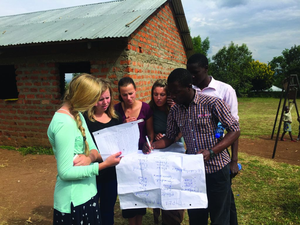 A photo of four nursing students studying a large piece of paper along with two locals from Kenya as one Kenyan writes on the paper.