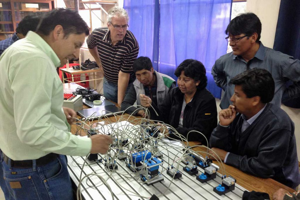 An image of some students in Bolivia learning about circuit boards.