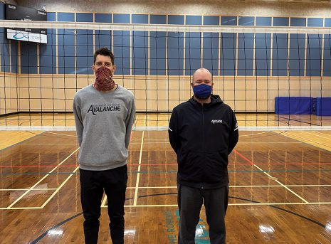 Image shows two men standing in front of a volleyball net in a gymnasium, both wearing masks.