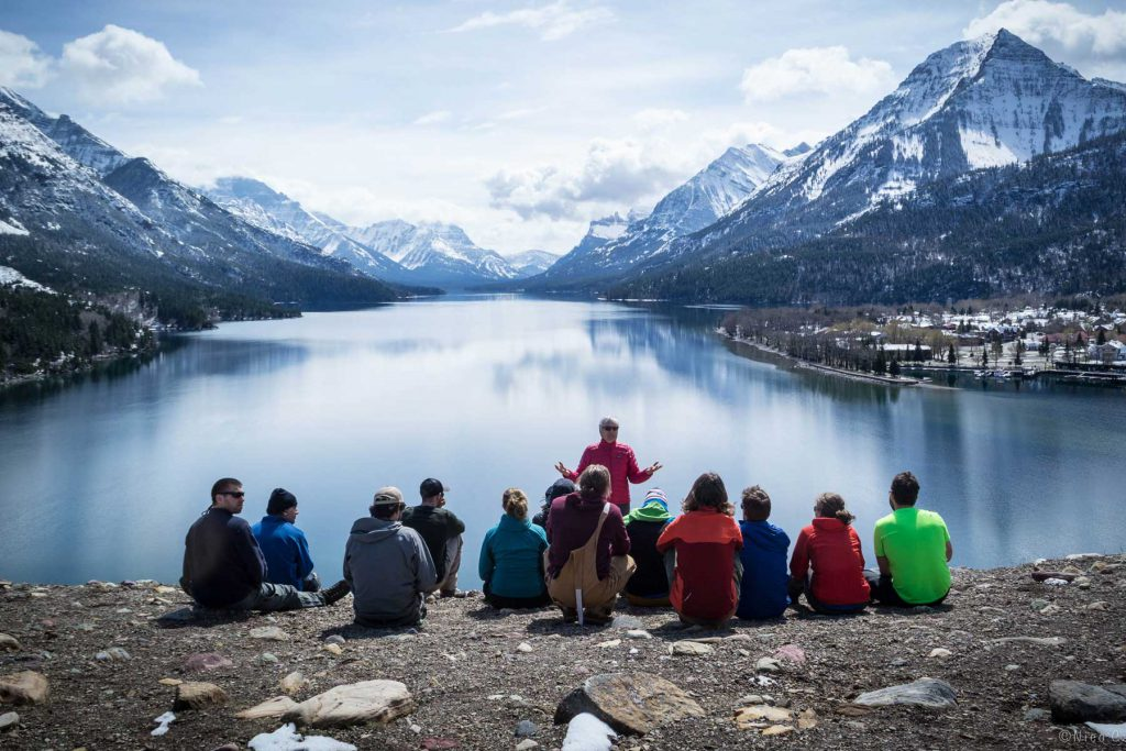 An image of a group of MAST students sitting at the edge of a lake.