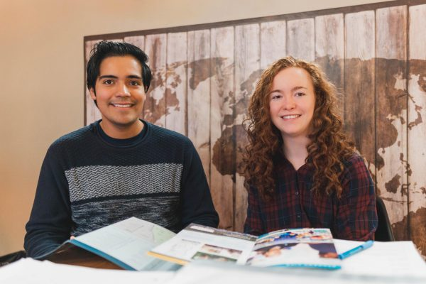 Image shows a young man and young woman sitting in front of a map of the world.