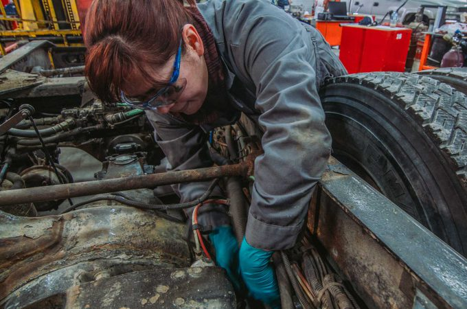 An image of a female heavy duty mechanic working on a machine.