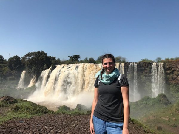 Image of young woman with Kenyan waterfall behind her.