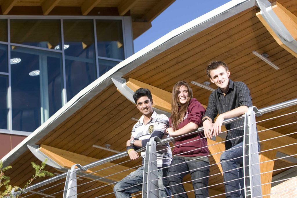 an image of three students standing outside the Cranbrook campus.