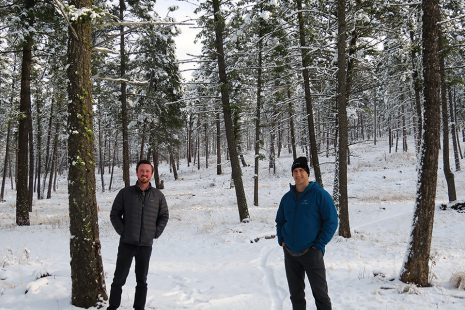 Image shows two men standing in snowy forest, simling at the camera.