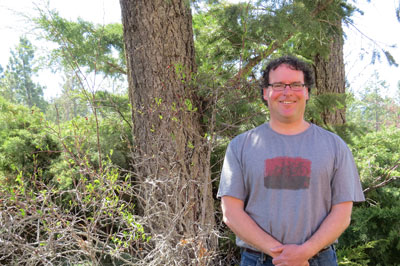 Image shows smiling man in glasses standing next to a tree and shrubs