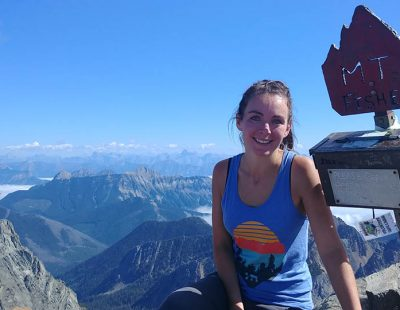 Image shows young woman smiling atop a mountain next to a sign reading Fisher Peak