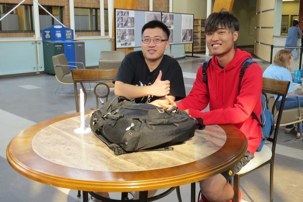 An image of two international students sitting at a table.