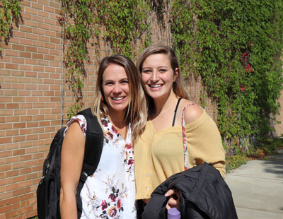 An image of two female students outside, smiling happily.