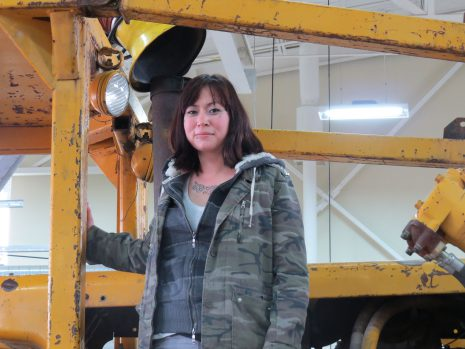 Image of a dark-haired woman standing on a large truck.