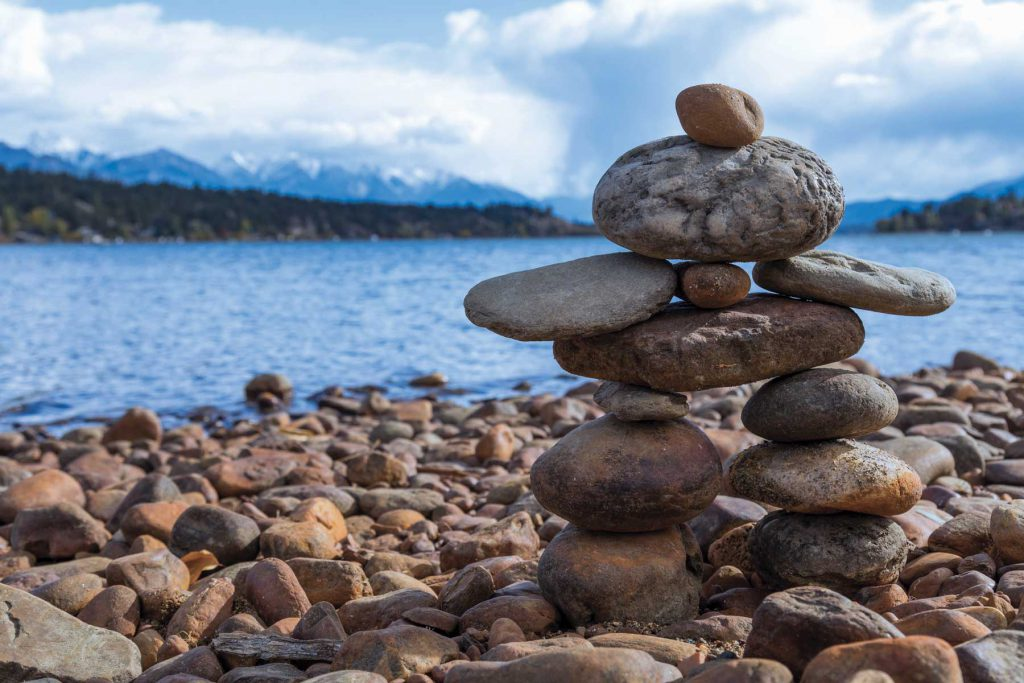 An image of an inukshuk with Lake Windermere in the background.