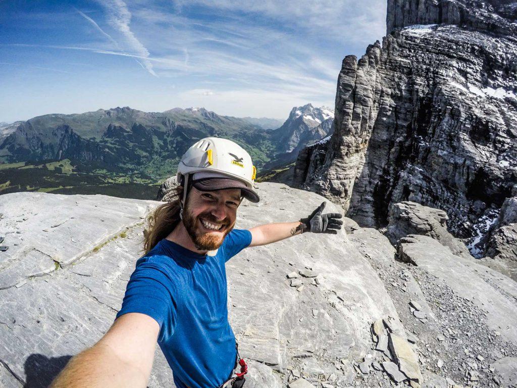 Image of man with helmet rock climbing.