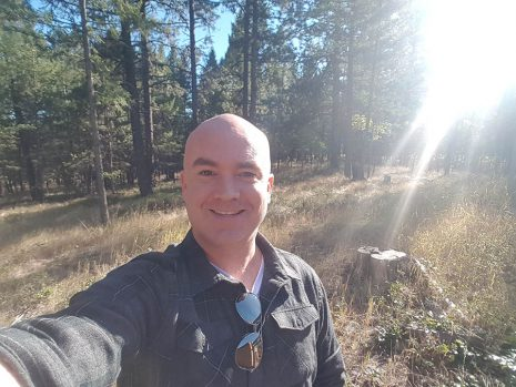 Image shows man smiling out in the woods with bright sunlight behind him.