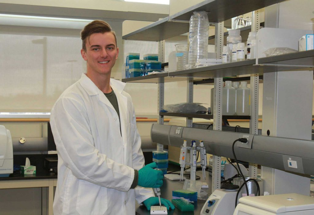 Image shows man in white lab coat and gloves in a lab setting.
