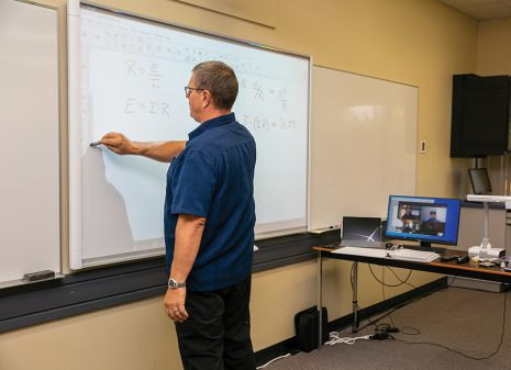 Image shows male instructor writing on a smart board with his students looking on via computer.