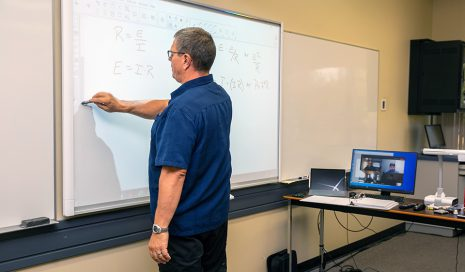 Image shows man standing writing on a Smartboard while students watch via a nearby computer.