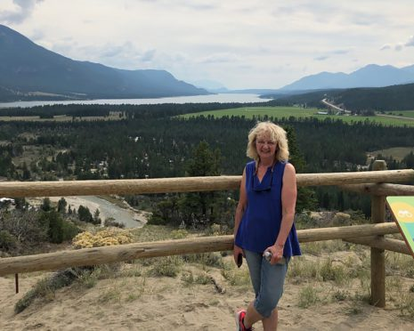 Image shows woman standing near a wooden fence at a lookout spot with a lake and mountains in the distance.
