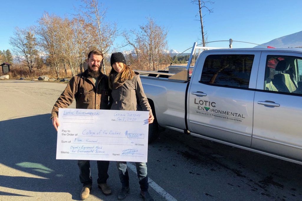 An image of the owners of Lotic Environmental stnading in front of a truck holding a large prop cheque.