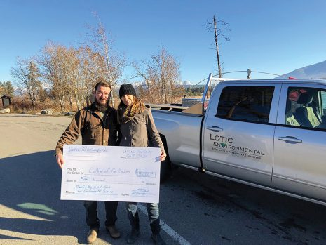 Mike and Corinna Robinson from Lotic Environmental hold a large cheque while standing in front of their company truck.