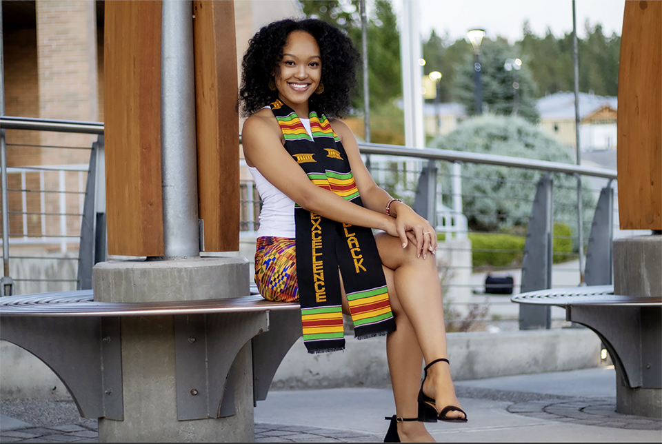Image shows woman wearing a colourful scarf sitting outside College of the Rockies.