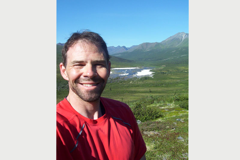 An image of a smiling man with fields and mountains in the background.