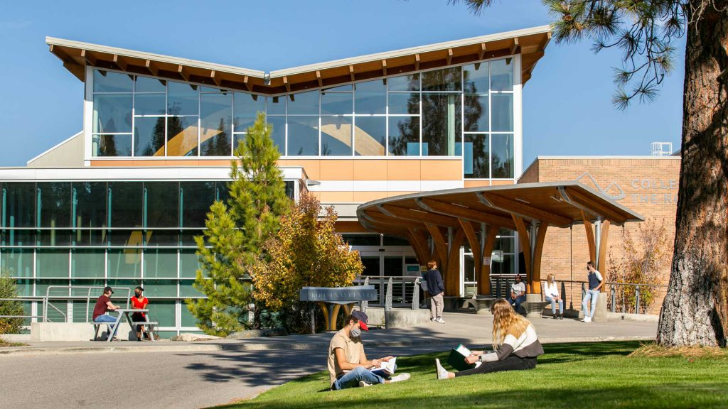 An image of students sitting ont eh grass outside College of the Rockies.