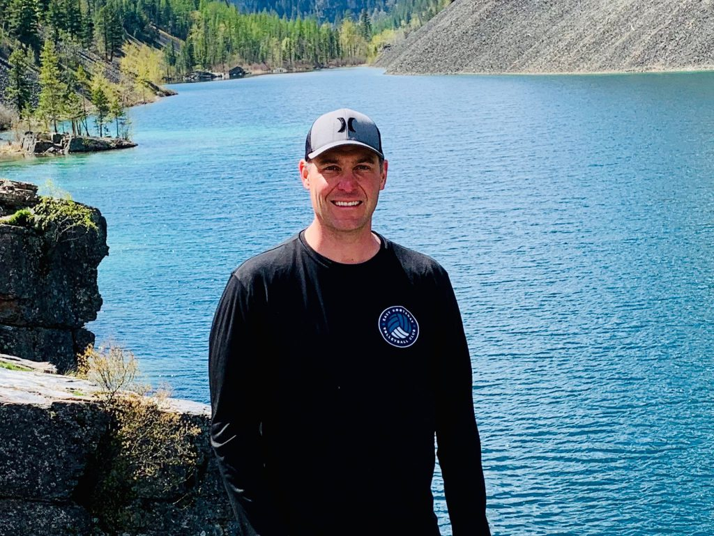 Image of Steve Kamps in ball cap and hiking clothes near a beautiful lake.