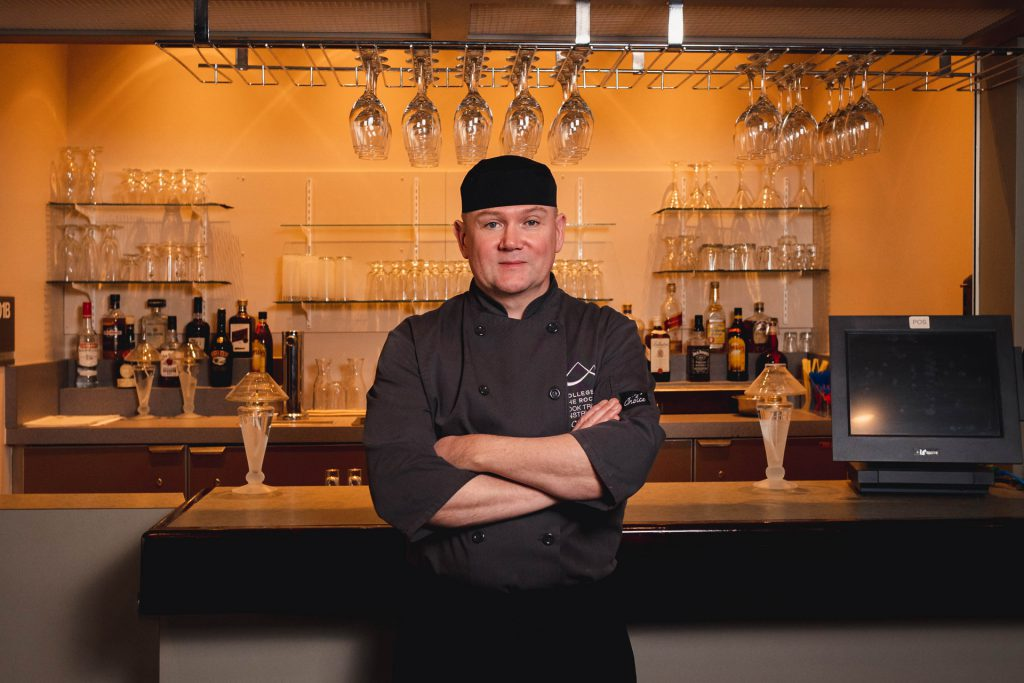Image shows man in chef's jacket standing with arms crossed in front of a bar.