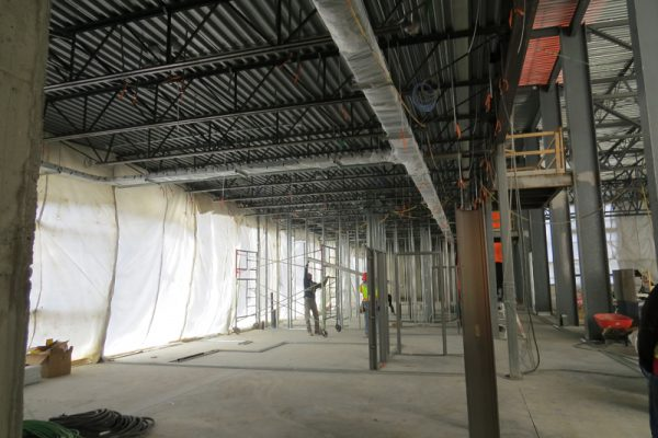 Image shows trades workers working inside building as it is being constructed.