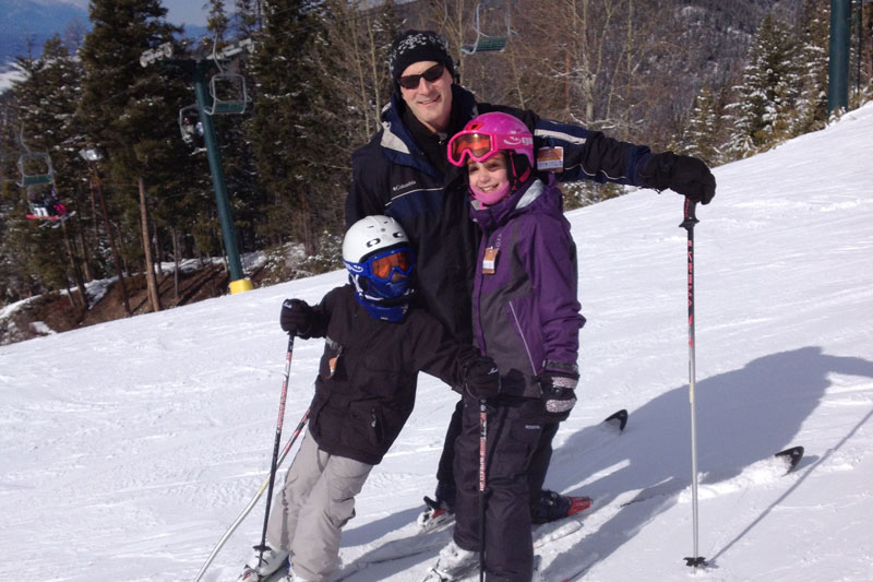 An image of a man and two children posing on a ski hill.