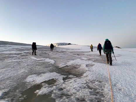Image shows individuals hiking on a glacier.