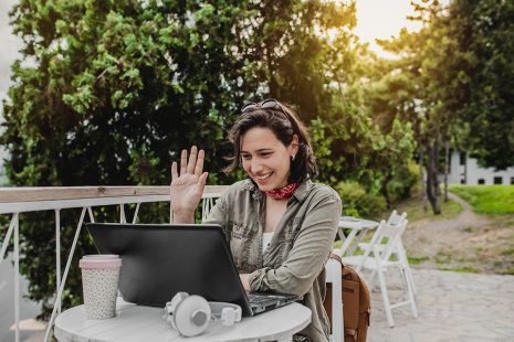 Image shows woman with a laptop open in front of her, smiling and raising her hand as if greeting someone on the screen.