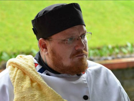 Image shows man with glasses wearing a black chef's cap and a white chef's jacket with a towel draped over his shoulder.