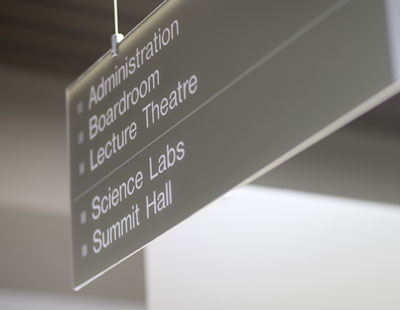 An image of a sign showing the direction of different departments at the College.