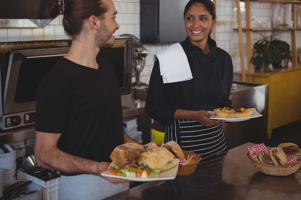 An image of two food service workers in a commercial kitchen.