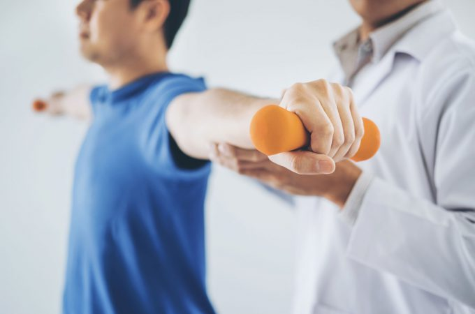 An image of a physical therapist helping a patient stretch.