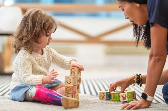 An image of an early childhood eductor and a toddler playing with blocks.