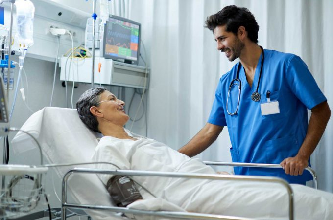 An image of a male nurse speaking with a patient in a hospital bed.