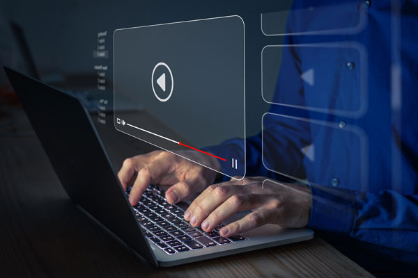 An image of a laptop and with a video prompt icon.
