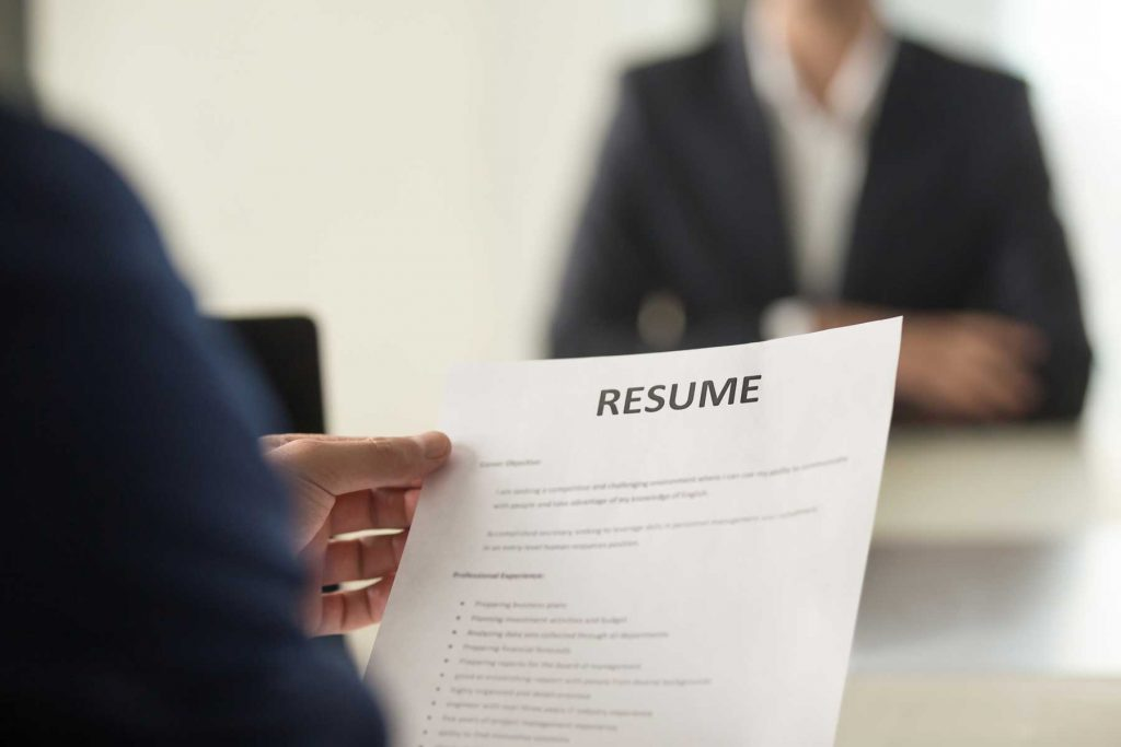 An image of a hand holding a resume.