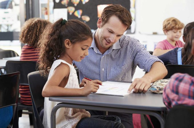 An image of a male grade school teacher assisting a student with her studies.