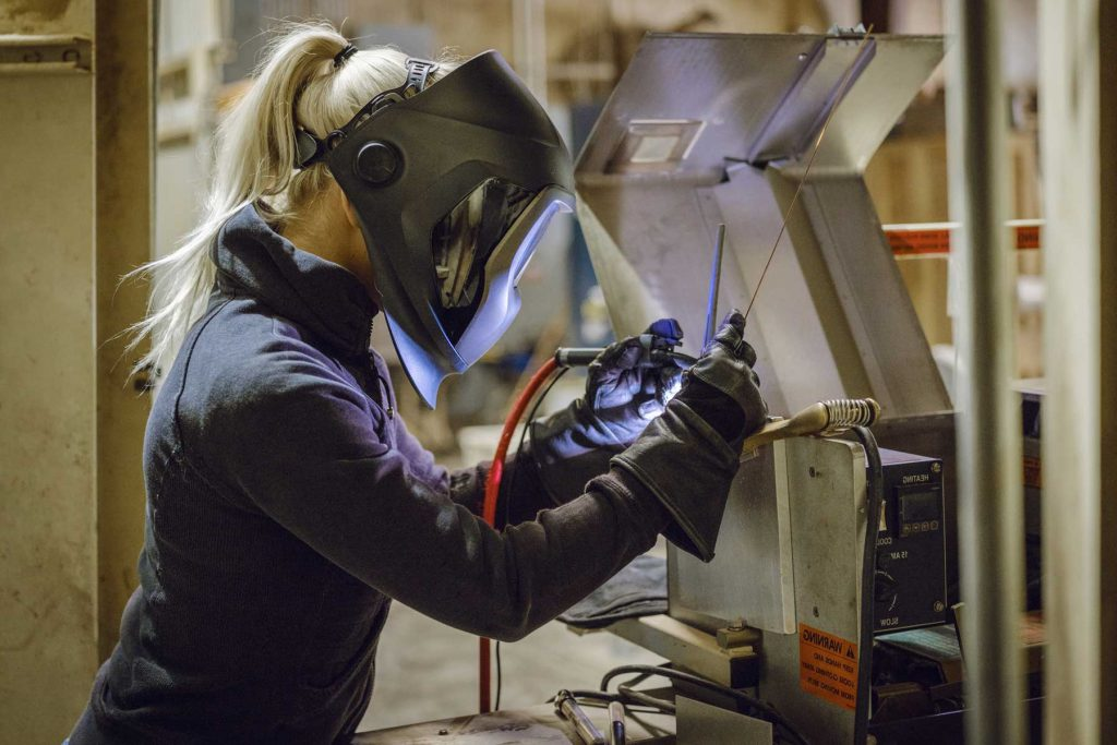 An image of a female welder wearing a mask and welding.