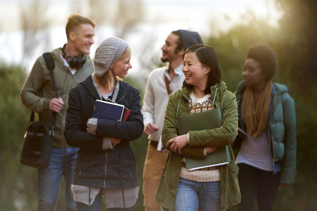 An image of five students walking together in a group outdoors.