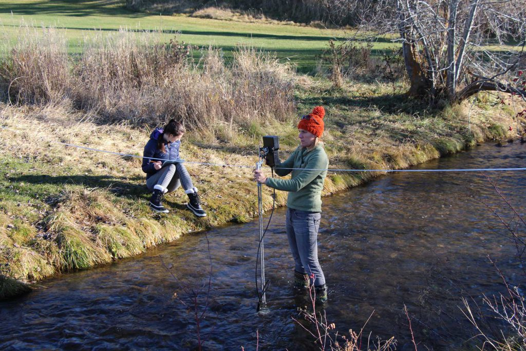 Image shows students doing field work in Joseph Creek in Cranbrook, BC.