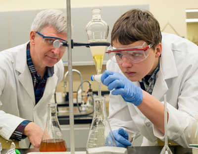 A student and instructor inside a science lab.