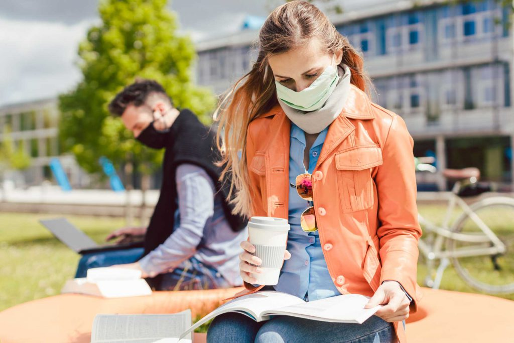 An image of two students wearing masks and looking at textbooks.