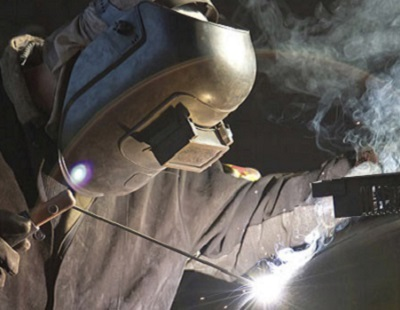 An image of a welding student with mask on using a welding torch to fuse two objects.